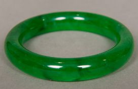 A Chinese carved spinach jade bangle 8.5 cm diameter.