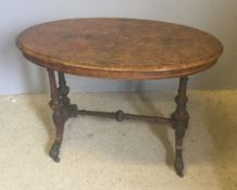 A Victorian inlaid burr walnut centre table The inlaid oval top standing on double turned and