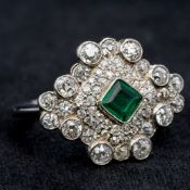 A platinum diamond and emerald cluster ring Of shaped navette form, centred with a single emerald.