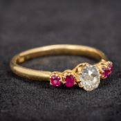An 18 ct gold diamond and ruby set ring The central stone approximately 0.5 carats.