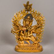 A gilt bronze model of a three faced multi-armed deity Holding a dancing girl with offerings,