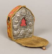A Tibetan unmarked white metal and copper travelling shrine Of typical form with repousse