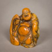 A Chinese carved soapstone seal Formed as Buddha, the underside with carved matrix. 8.5 cm high.