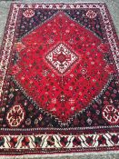 A wool rug The wine red field enclosing a central medallion,