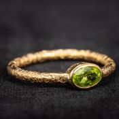 A 19th century unmarked gold peridot set ring The shank with all round engraved decoration.