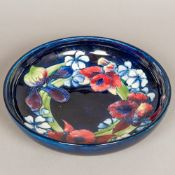 A William Moorcroft Orchid pattern fruit bowl Of shallow form, standing on a circular foot,