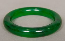 A Chinese carved spinach jade bangle 8 cm diameter.