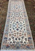 A Kashan wool runner The ivory field enclosing arabesque vines within floral border. 313 x 102 cm.