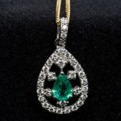 An 18 ct white gold diamond and emerald pendant Of pierced drop form,
