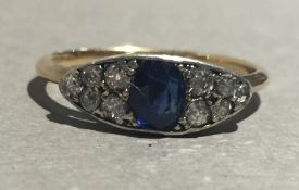 An unmarked gold diamond and sapphire navette form ring