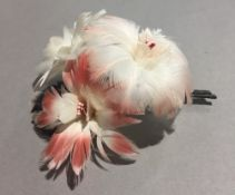 A boxed flamingo feather brooch