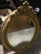 A gilt framed oval mirror