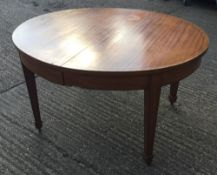 A late 19th/early 20th century oval satinwood extendable dining table