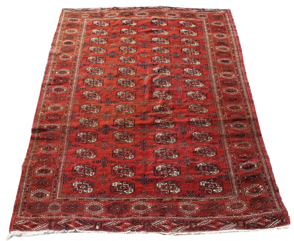 Lot 20 - Property of a lady - a mid 20th century Turkoman carpet with four rows of octagonal guls on a red