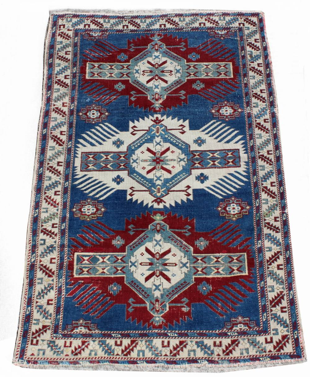 Lot 40 - Property of a deceased estate - an early 20th century Caucasian Kazak rug, with navy field, 76 by