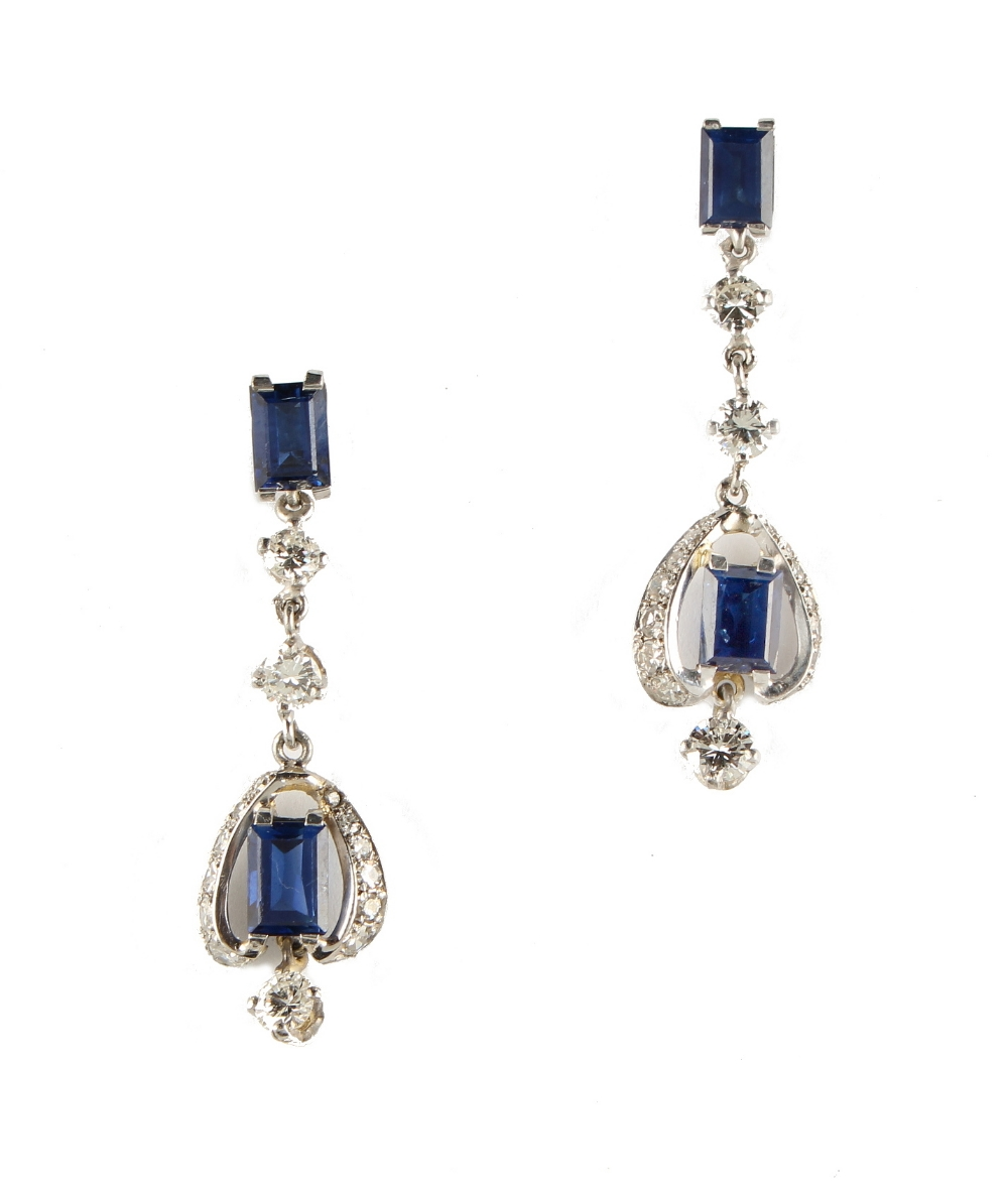 Lot 235 - A pair of sapphire & diamond pendant drop earrings, each with two rectangular cut sapphires &