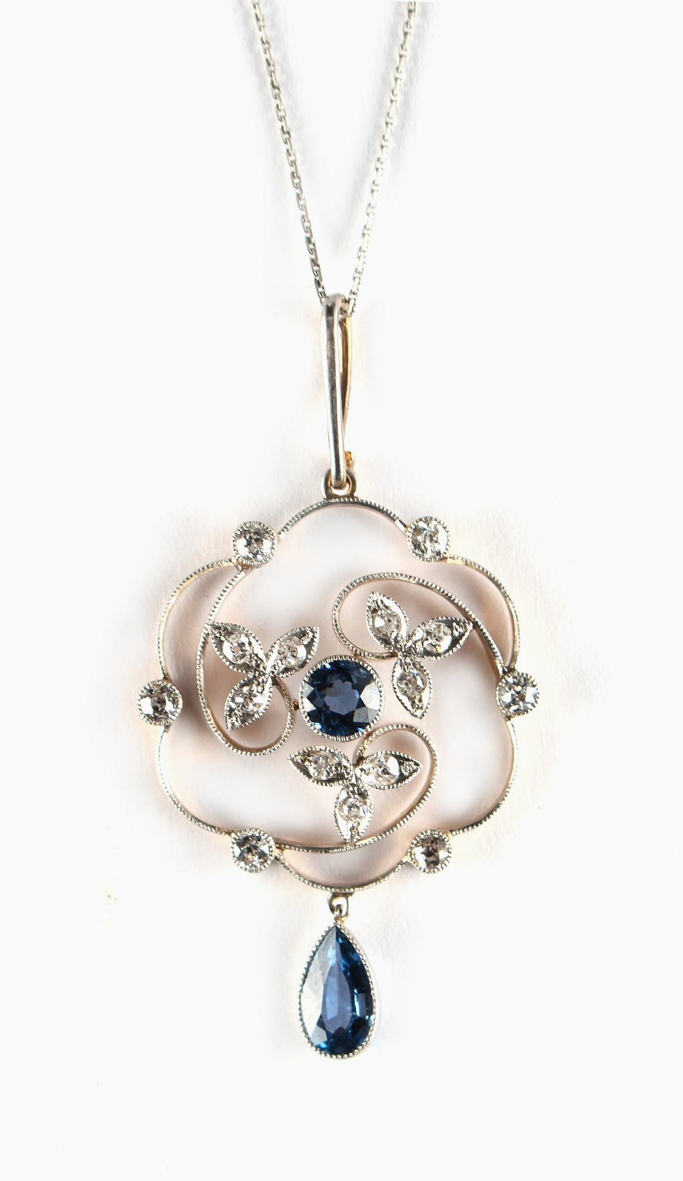 Lot 260 - An early 20th century Belle Epoque sapphire & diamond floral open work pendant on later chain, the