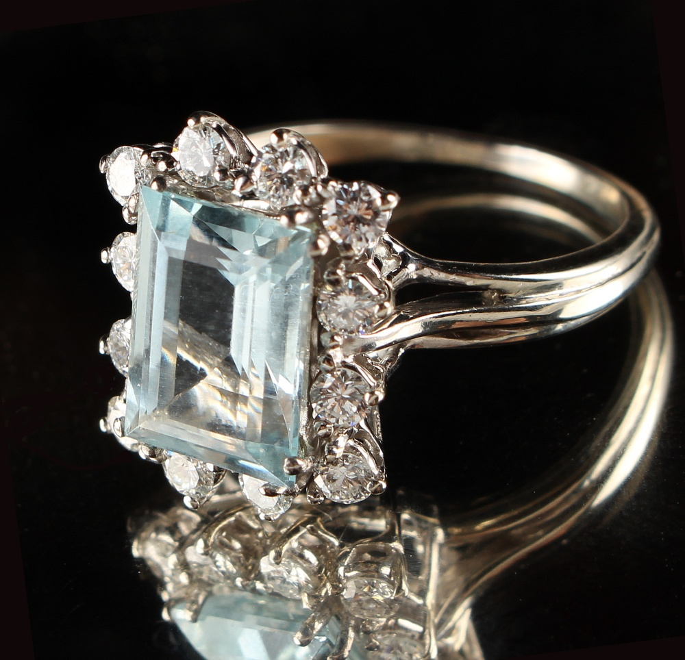 Lot 256 - An unmarked white gold aquamarine & diamond ring, the rectangular cut aquamarine weighing an