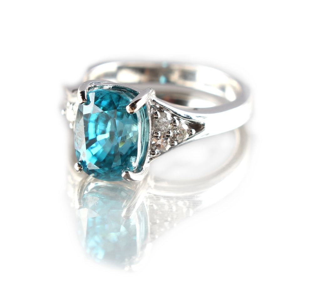 Lot 225 - An unmarked white gold or platinum zircon & diamond ring, the oval cut zircon weighing approximately