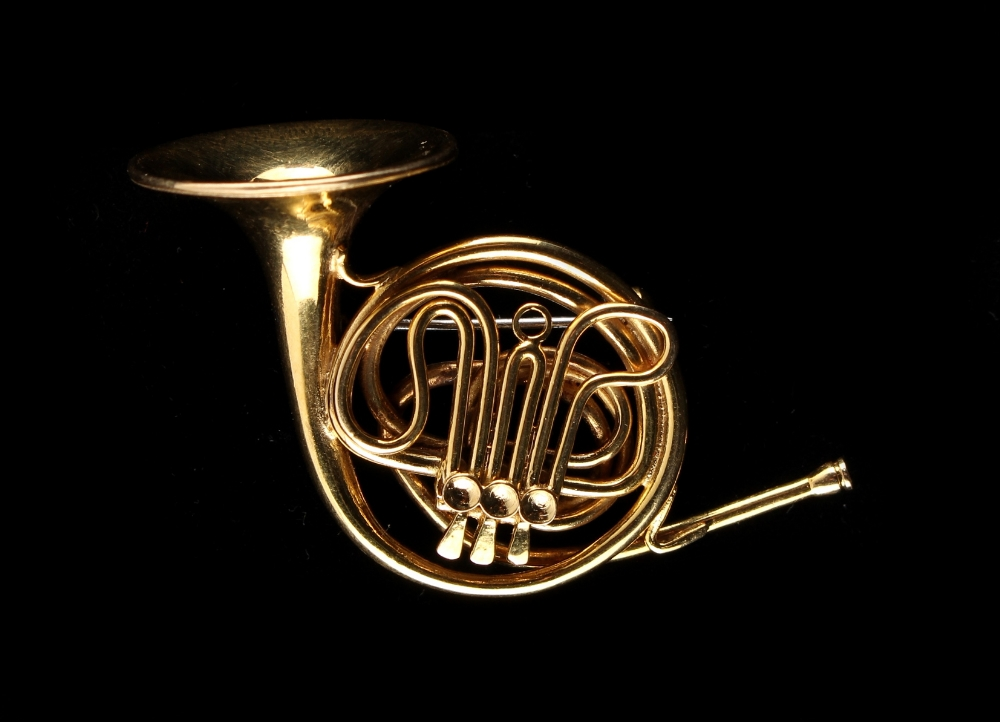 Lot 220 - Cartier - an 18ct yellow gold brooch modelled as a French horn, hallmarked Jacques Cartier, London