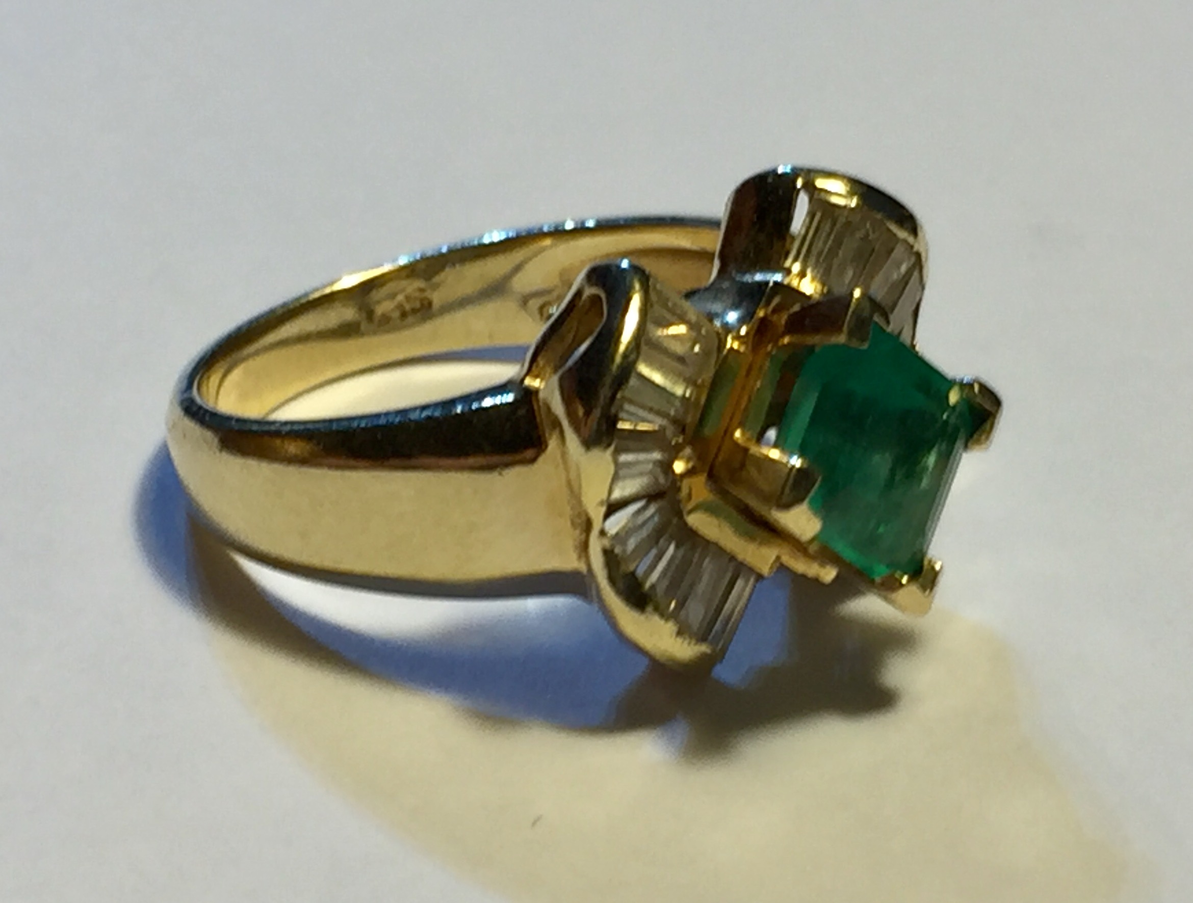 Lot 16 - A 14CT GOLD, DIAMOND AND EMERALD RING Having a single cushion cut emerald flanked by baguette cut