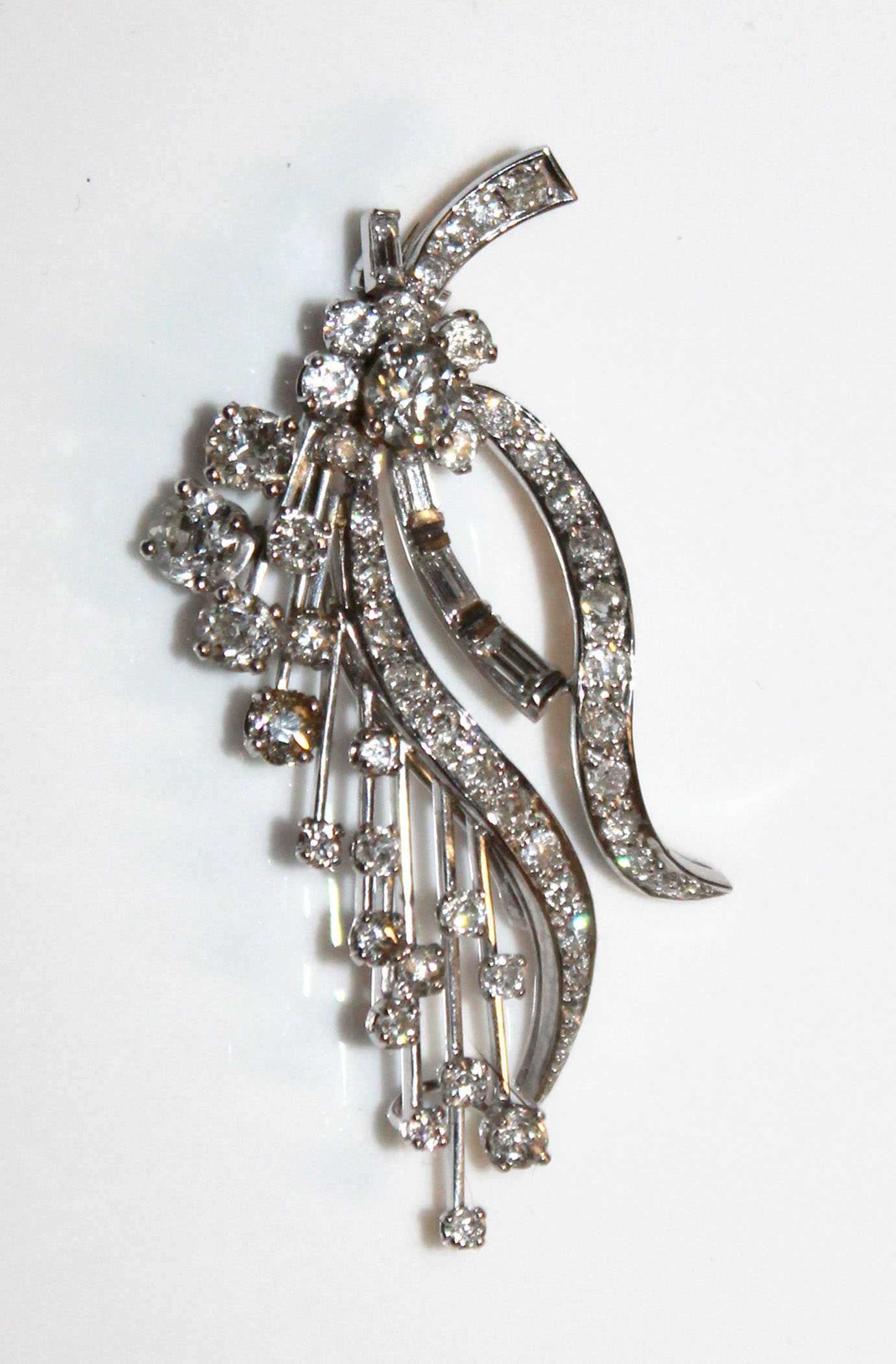 Lot 34 - A VINTAGE PLATINUM AND DIAMOND BROOCH The arrangement of round and baguette cut diamonds forming a
