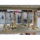 A mixed lot of brass candlesticks including barley twist and a trivet.
