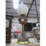 A brass oil lamp complete with shade and chimney.