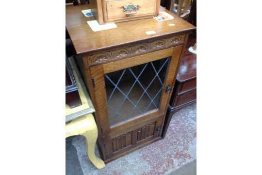 An Oak Hi Fi Cabinet With Leaded Glass And Linen Fold Panel Doors