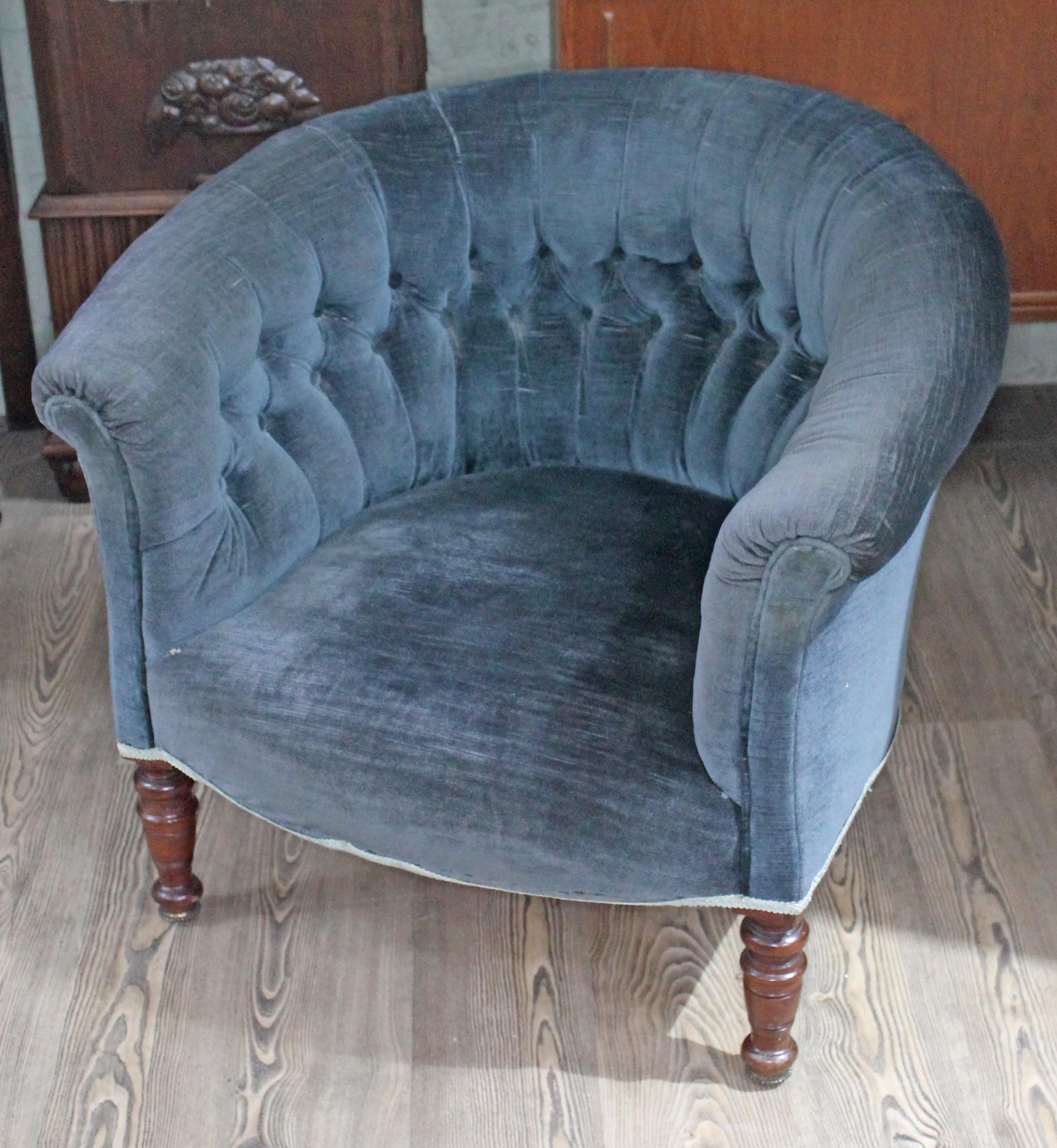 A Victorian buttoned blue upholstered tub with scroll arms and back ...
