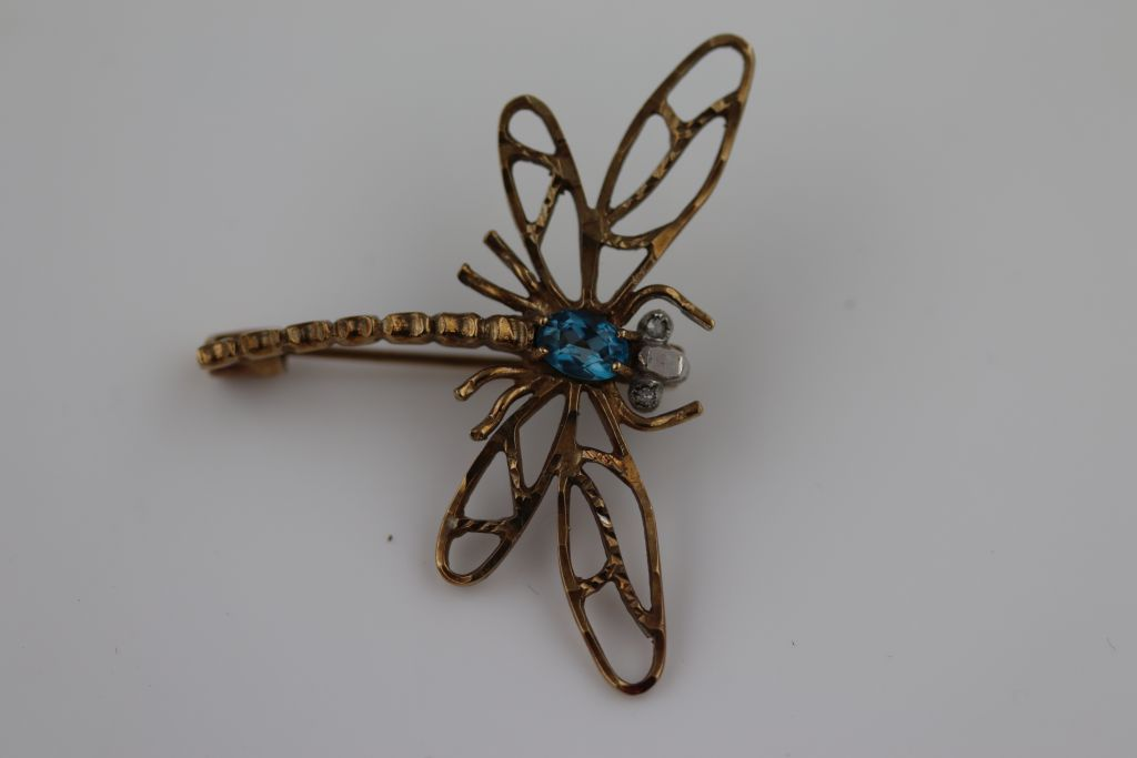 Lot 23 - A blue topaz yellow metal dragonfly brooch, white stone eyes, approximately 32mm by 42mm, tests as