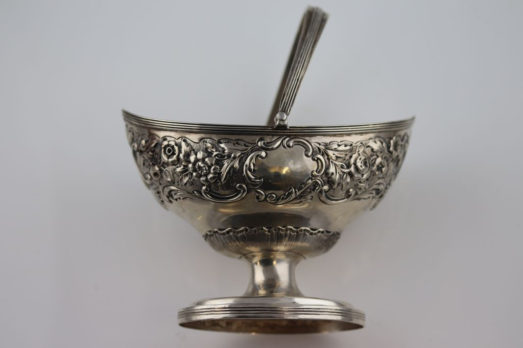 Lot 5 - A George III silver swing handled sugar basket of navette form, repousse garland style floral and