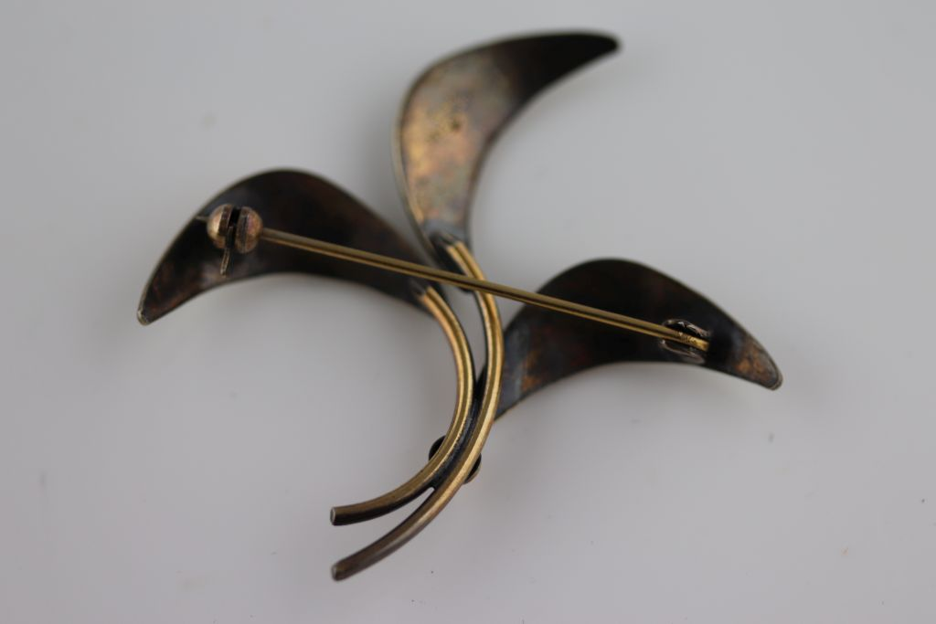 Lot 31 - A Scandinavian style enamelled silver gilt vintage three leaf brooch, white enamelled leaves (some