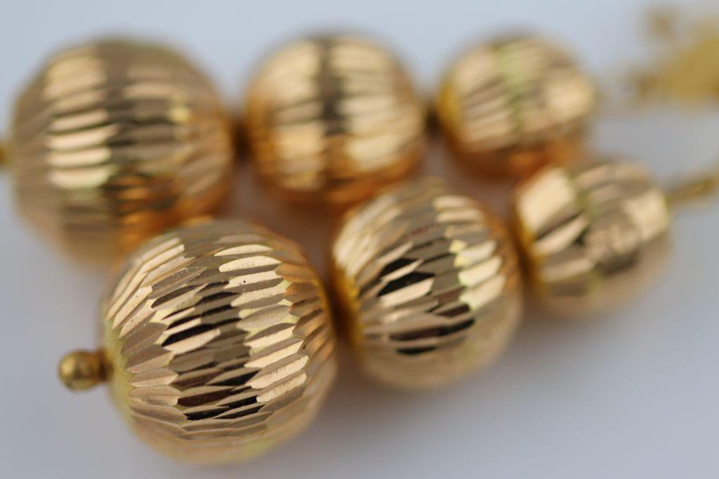 Lot 21 - A pair of yellow metal drop earrings, three graduated textured spheres, shepherd hook ear