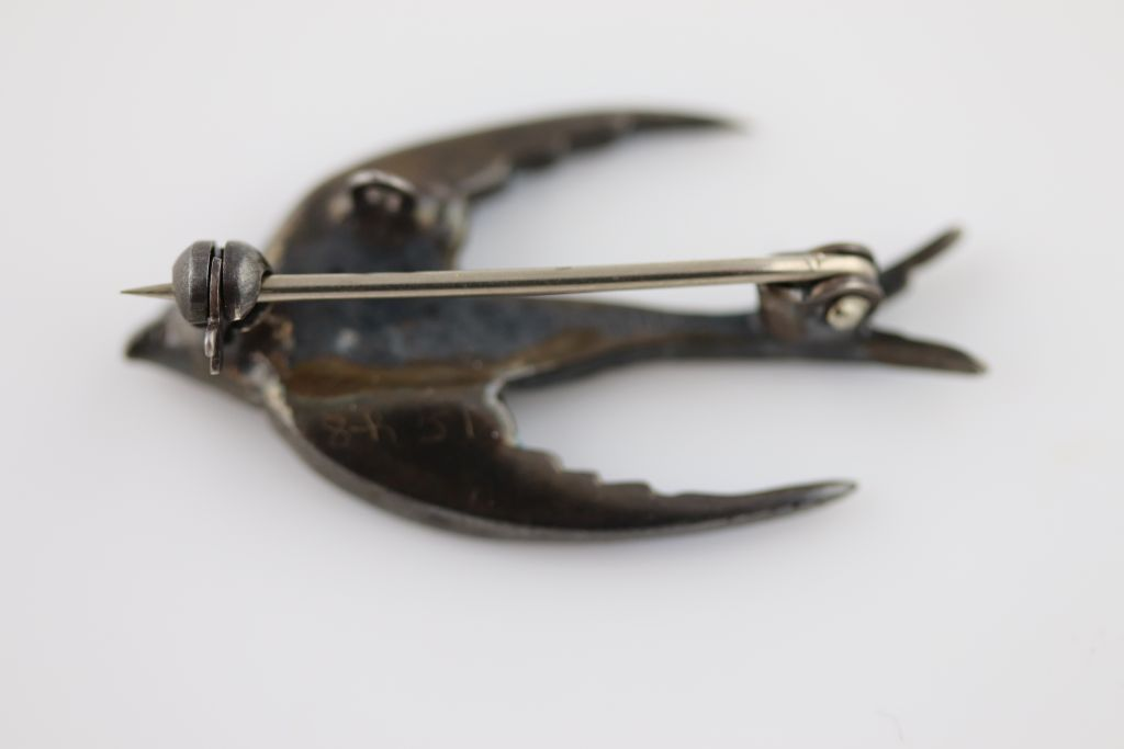 Lot 42 - An enamelled, marcasite and paste silver swallow brooch, in flight, blue enamelled wings and tail,