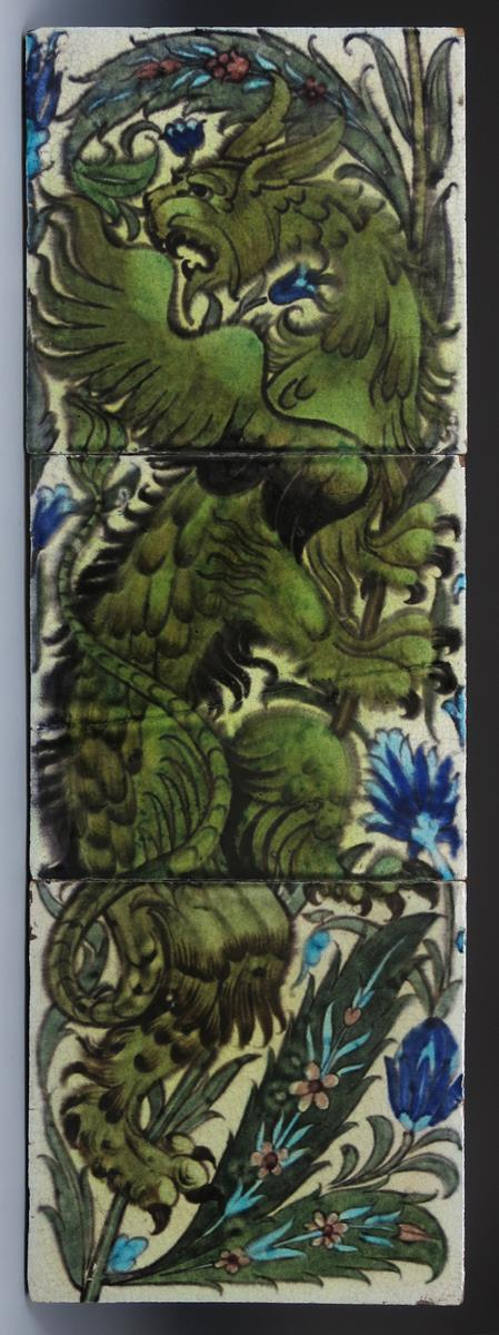 A William De Morgan Persian three tile panel, painted with a dragon climbing a bough, in shades of