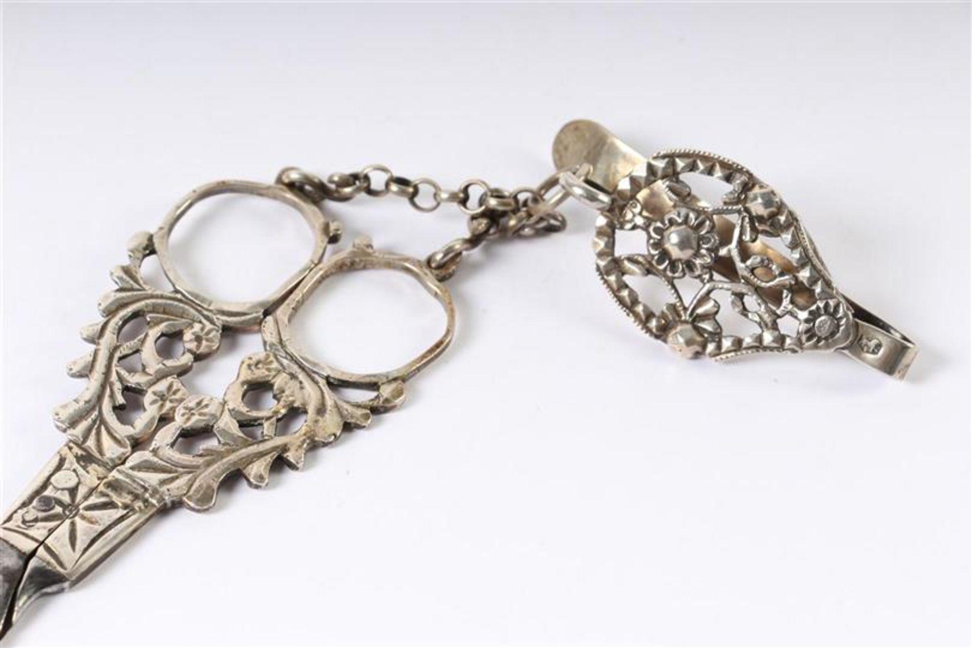 Los 30 - Zilveren broekhaak met hieraan een schaar en een zilveren naaldenkoker, Hollands gekeurd. L: 22 en