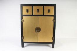Zwart met goudkleurig houten kastje in Oosterse stijl. HxBxD: 82 x 63 x 26 cm.