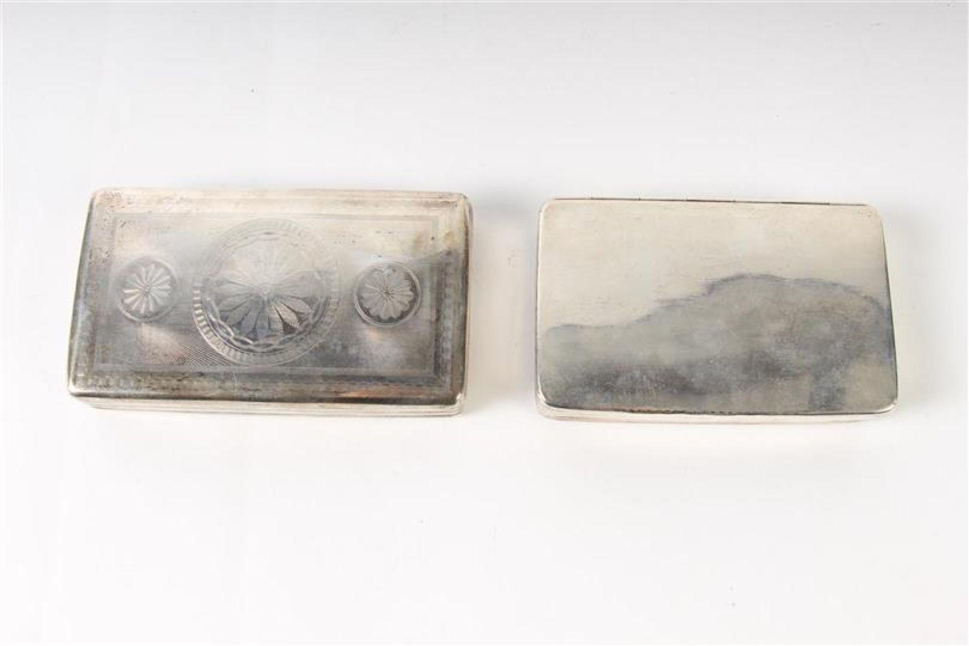 Twee zilveren tabaksdozen, Hollands gekeurd. HxBxD: 7 x 12.5 x 2.5 en 7 x 11.3 x 2.3 cm.