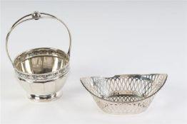 Zilveren hengselmandje en eenzilveren bonbonmandje met onderbrokenparelrand. Gewicht: 200 g.
