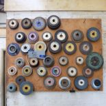 Lot 56 - Assorted Used Grinding Wheels on wall rack and bench.