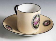 Moccatasse mit Untertasse, Porzellan, auf beigem Grund polychrome Rosenmalerei, die Ränder schwarz