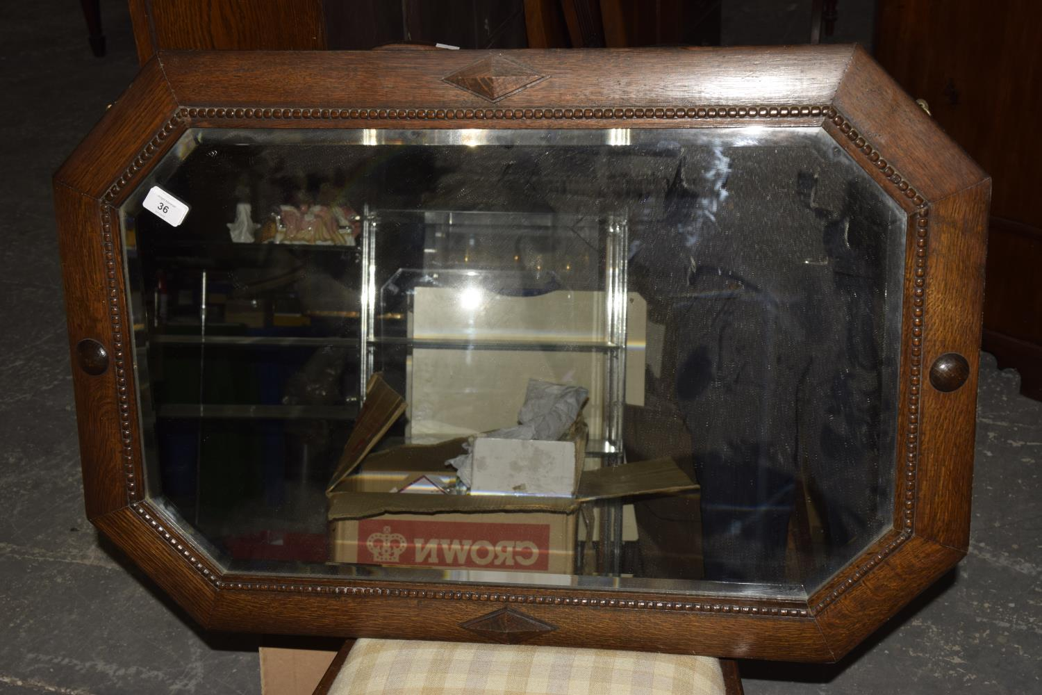 Lot 36 - An Art Decco oak octagonal wall mirror The wall mirror with beading surround and beveled mirror