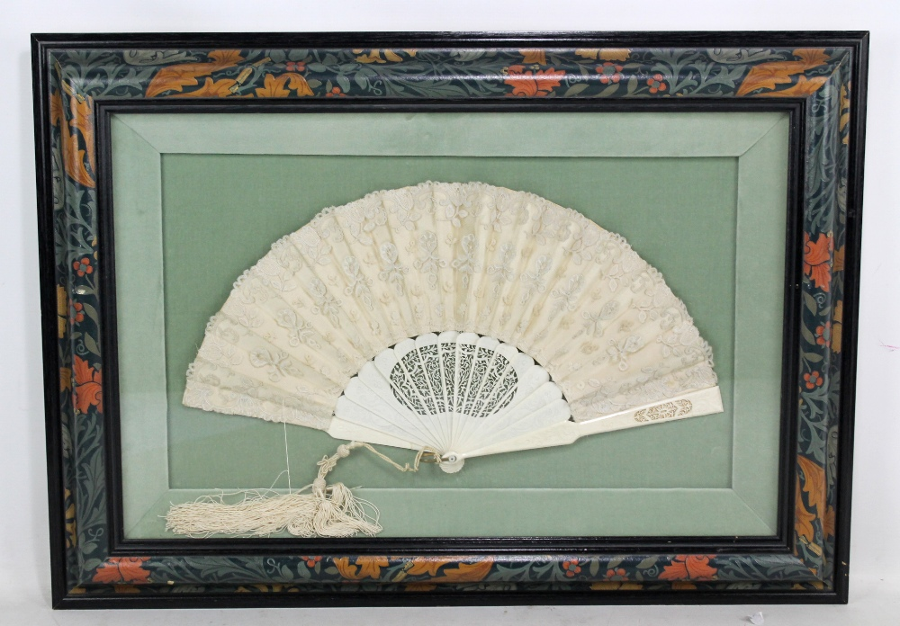 Lot 8 - An ivory and lace fan with pierced and foliate detail, width approx 50cm, framed and glazed.