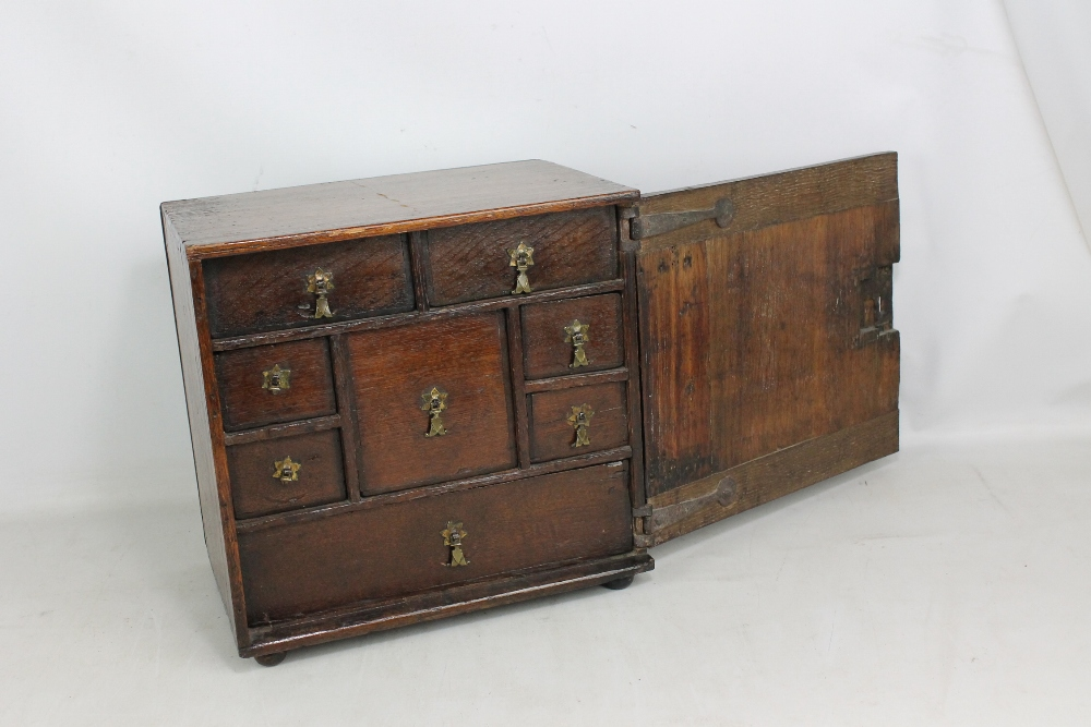 Lot 49A - An early 18th century oak spice cabinet with geometrically moulded hinged door enclosing an