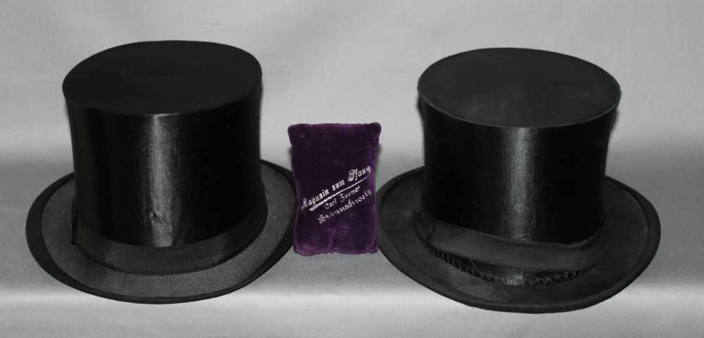 """Lot 5 - Mode. Zwei Klappzylinder """"Chapeau Claque""""in zeitgenössischer Pappschachtel. Viereckige Pappschachtel"""