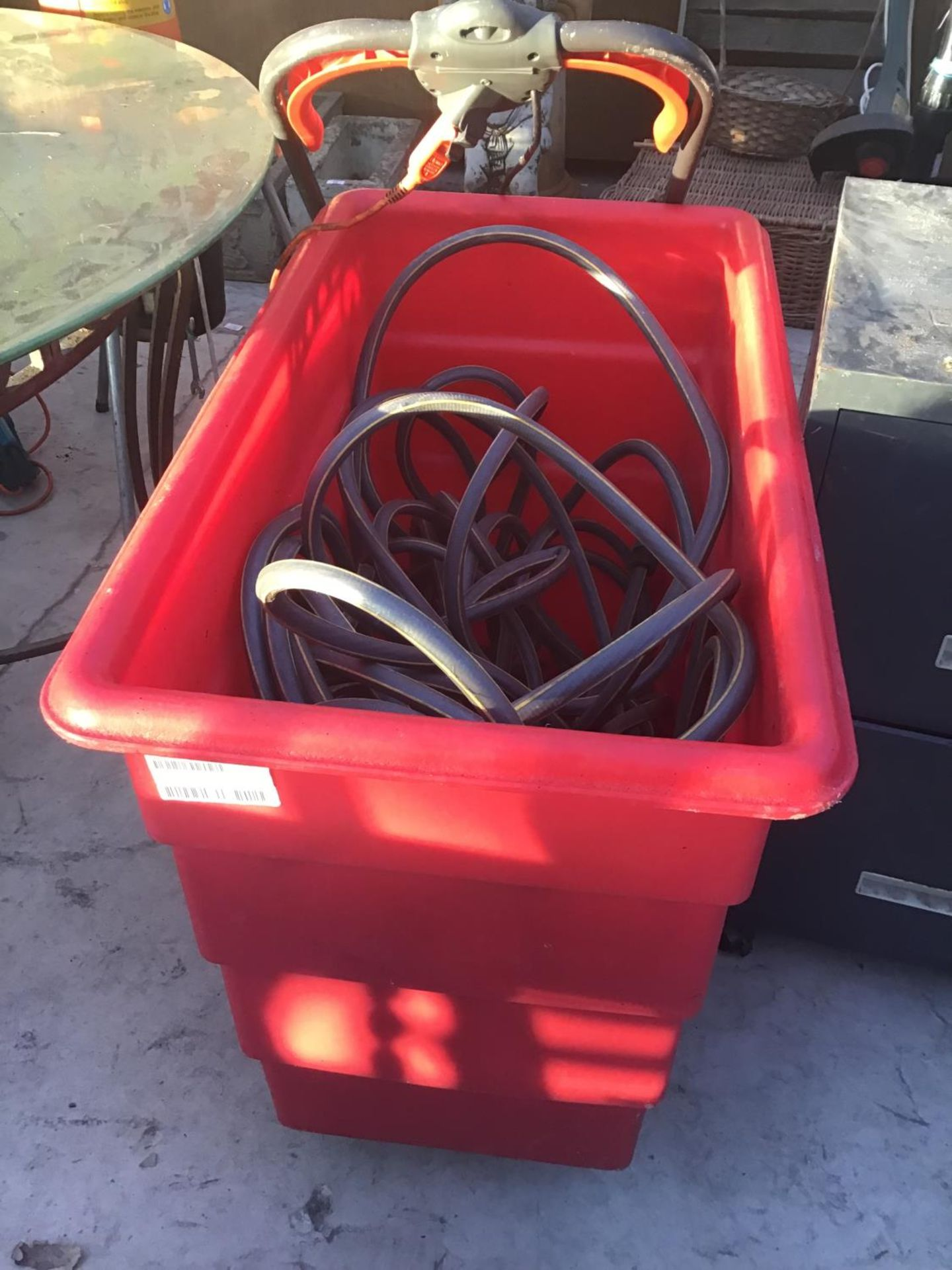 Lot 203 - A RED PLASTIC TUB ON WHEELS WITH A HOSE PIPE