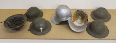 A collection of metal helmets with five being of a military style,