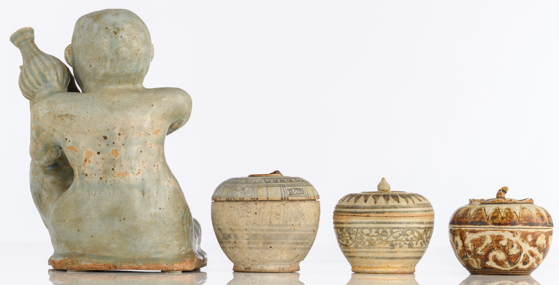 Lot 22 - A Longquan type celadon figure holding a jug; added three Sui earthenware type covered jars, H 8,5 -