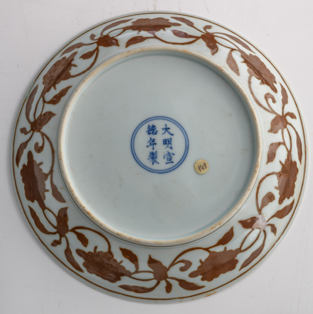 Lot 35 - A Chinese copper red plate, decorated with lotus flowers, pomegranates, peaches, and persimmons,